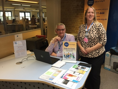 Photograph – Clive Bolland, Help to Claim Adviser, Citizens Advice IW and Heidi Widgery, Newport Jobcentre Customer Services Manager.  Clive is sat at a desk with a laptop in front of him and a posted with Help To Claim on it next to him. On the othe